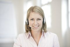 Receptionist. Woman with headphone smiling with blond hair, officesituation royalty free stock images
