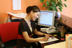 Receptionist. A woman receptionist working hard at the front desk Stock Photography