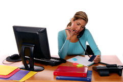 Receptionist. Sexy Latin business woman working at her computer desk with colorful file folders while placing a credit card order over the telephone Royalty Free Stock Images