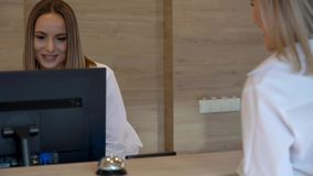 Receptionist assisting hotel guest at desk