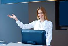 Receptionist attraente della donna che fa gesto amichevole Immagine Stock