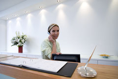 Receptionist behind desk with headset Stock Photos
