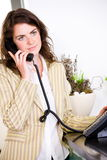 Receptionist calling on phone. Young female receptionist receiving phone calls at office reception royalty free stock image