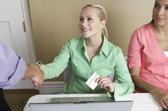 Receptionist Distributing Name Tags Royalty Free Stock Photography