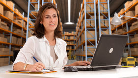 Receptionist at distribution warehouse b. Female administrative in a desk with a distribution warehouse in the background royalty free stock image