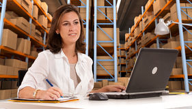 Receptionist at distribution warehouse. Female administrative in a desk with a distribution warehouse in the background royalty free stock image