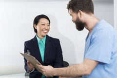 Receptionist And Doctor Discussing Over Clipboard. Happy receptionist and doctor discussing over clipboard in hospital Royalty Free Stock Images