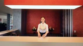 Receptionist femminile che sorride e che dà carta chiave all'ingresso dell'hotel video d archivio