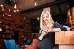 Receptionist femminile del salone di bellezza con lo smartphone immagini stock
