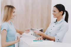 Receptionist Gives Customer Business Card in Salon. Woman Receptionist. Business Card in Salon. Workplace in Beauty Salon. White Interior. White Reception Desk stock photo