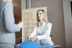 Receptionist giving file to businessman at convention center royalty free stock photos