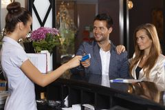 Receptionist giving key card to guests at hotel