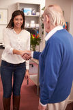Receptionist Greeting Senior Male Patient At Hearing Clinic Stock Photo