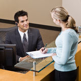 Receptionist greeting woman at front desk Royalty Free Stock Photos
