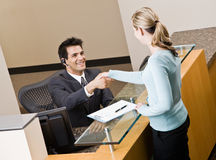 Receptionist greeting woman at front desk Stock Photography