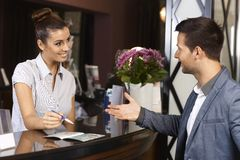 Receptionist and guest at hotel. Happy receptionist and guest talking at hotel reception Stock Photo