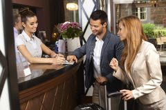Receptionist and guests at hotel. Receptionist giving tourist information to hotel guests upon arrival