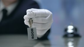 Receptionist hand holding keys to hotel room, booking concept, luxury services. Stock footage stock video footage