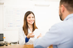 Receptionist handing results to patient. Pretty receptionist handing over lab test results to a patient with a smile Stock Photo