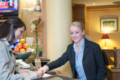 Receptionist helping a hotel guest check in. Smiling attractive young receptionist helping a hotel guest check in pointing to information on the form that needs Royalty Free Stock Photos