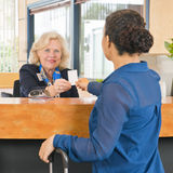 Receptionist helping a newly arriving hotel guest Stock Photo