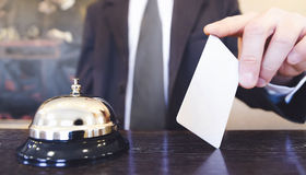 Receptionist holding a card. Hotel receptionist holding a blank room key card Stock Image