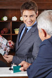 Receptionist in hotel giving brochure to guest Stock Photo