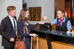 Receptionist at hotel reception handing over key to guest or cus Stock Photo