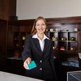 Receptionist i hotellet som erbjuder det nyckel- kortet Royaltyfri Foto