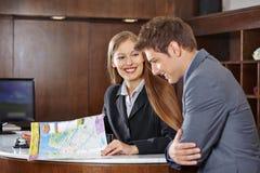 Receptionist i hotellportiongäst med stadsöversikten Arkivbilder