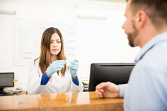 Receptionist labeling sample in a laboratory. Good looking receptionist labeling a urine sample from a male patient in a laboratory front desk Royalty Free Stock Photography
