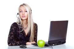 Receptionist with laptop. A view of a young blond receptionist or administrative person with a headset and microphone, sitting in front of a laptop computer and Royalty Free Stock Photos