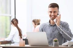Receptionist maschio che parla sul telefono allo scrittorio fotografia stock