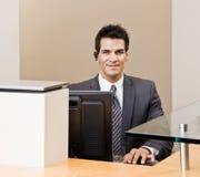 Receptionist maschio con il ricevitore telefonico di telefono immagini stock libere da diritti