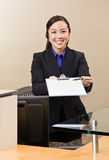 Receptionist offering clipboard and pen Stock Photo
