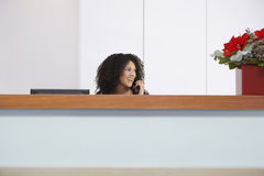 Receptionist On Call Behind Reception Desk