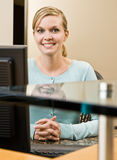 Receptionist posing at front desk Stock Images