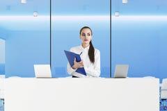 Receptionist rigoroso con la lavagna per appunti in ufficio blu Immagini Stock Libere da Diritti