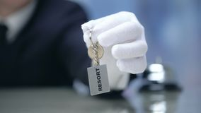 Receptionist showing keychain with Resort word, luxury property rental, closeup. Stock footage stock footage
