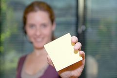 Receptionist shows sticky note. Female model holding a blank sticky note for your text.  Narrow depth of field, sharp focus on sticky note Royalty Free Stock Images