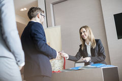 Receptionist som ger identitetskortet till affärsmannen på konventcentret royaltyfria bilder