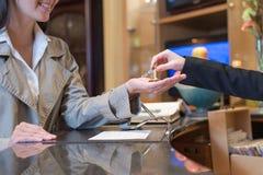 Receptionist som räcker över tangenter till hotellrum Arkivbild