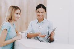 Receptionist sorridente Shows Client Tablet in salone fotografia stock