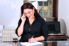 Receptionist taking note. While answering a phone Royalty Free Stock Photography