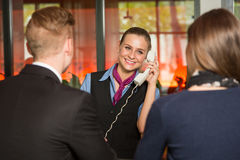 Receptionist with telephone assisting guests in hotel Royalty Free Stock Photo