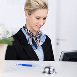 Receptionist Using Computer At Desk Royalty Free Stock Image