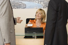 Receptionist working behind reception desk, receiving business card from businessman, smiling Royalty Free Stock Image