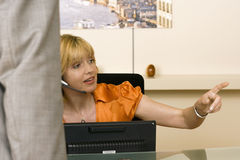 Receptionist working behind reception desk, showing businessman the way, pointing finger Royalty Free Stock Photo