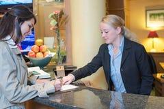 Receptionisten som hjälper en hotellgäst, kontrollerar in Arkivfoto