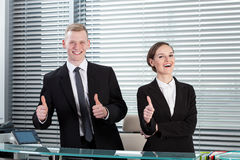 Receptionists showing thumbs up sign. Smiling receptionists showing thumbs up sign Royalty Free Stock Photo